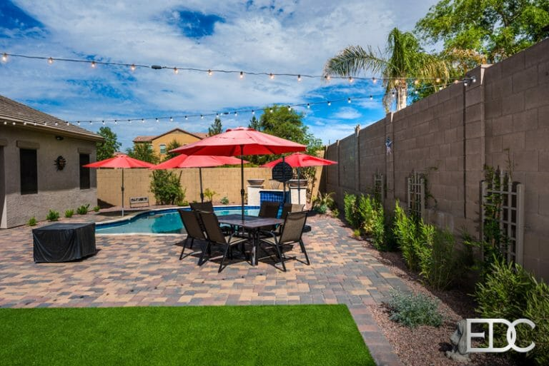 Pool with wall sheer decent, concrete pavers and turf in