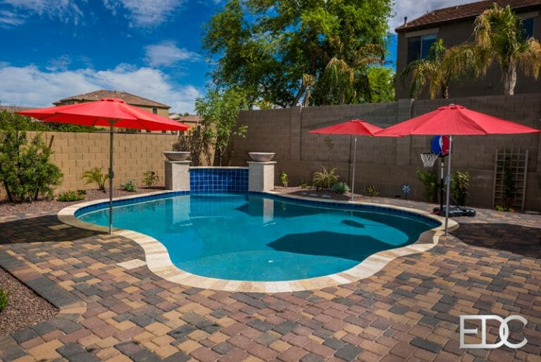 Pool with wall sheer decent concrete pavers and turf in for Pool design companies