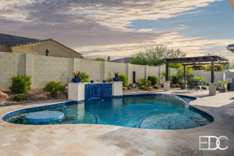 Custom Swimming Pool With Water Feature Table Top And Bench Seating Pergola Tavertine Decking And Built In Bbq In Gilbert Az